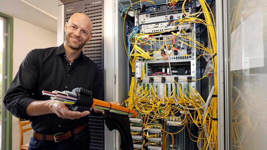 Christian Palla ist zuständig für den Ausbau des Glasfasernetzes und zeigt eine neue Schaltzentrale.