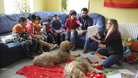 Susanne Rehn (rechts) zeigt auch anhand von Bildern, was man berücksichtigen sollte, damit sich Hund und Mensch verstehen. Ramsi Ali (2.v.r.) hilft mit Übersetzungen.