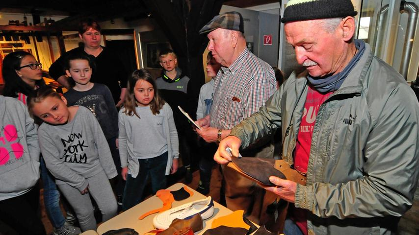 So wird das Leder für den Schuh über den Holzleisten gelegt. Georg Seeberger (rechts) demonstriert es den Workshop-Teilnehmern im Stadtmuseum, Robert Keller (neben Seeberger) erklärt das Prozedere der Schuhproduktion.